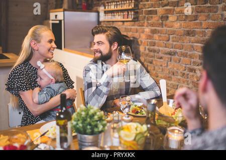 La famiglia e gli amici di gustare la cena, mangiare, bere, divertendosi Foto Stock