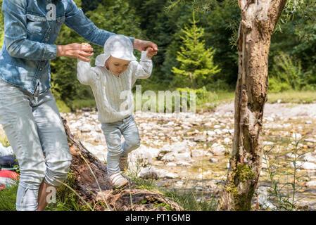 Madre tenendo le mani della figlia, bilanciamento sul tronco di albero Foto Stock