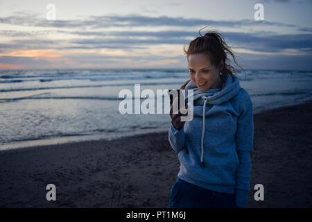 Donna che utilizza smartphone sulla spiaggia al tramonto
