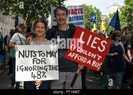 """Sorridente coppia giovane su anti Brexit rally portando cartelli 'dadi a maggio per ignorare il 48%' e 'bugie non potevo permettermi un bus"""". Foto Stock"""
