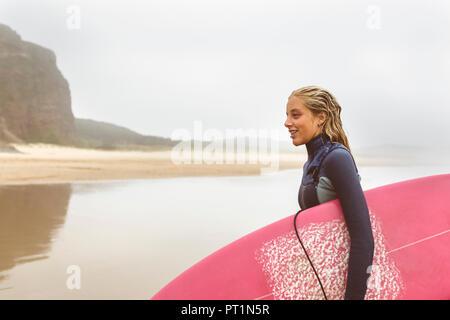 Spagna, Aviles, giovani surfer proveniente dall'acqua sulla spiaggia Foto Stock