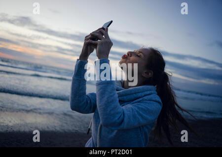 Donna che utilizza smartphone sulla spiaggia al tramonto, invio di kiss