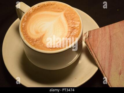 Amore caffè, una tazza di latte art con modello cuore in una tazza bianca Foto Stock