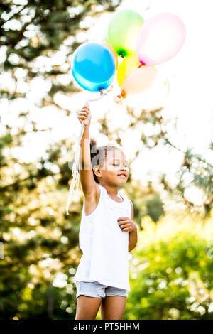 Ragazza con mazzo di palloncini in park. Foto Stock