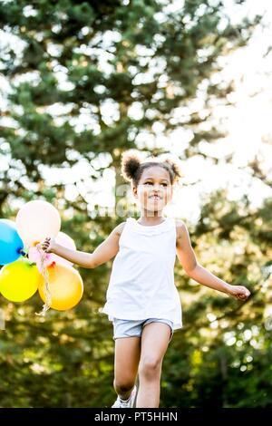 Ragazza in mazzetti in esecuzione con palloncini nel parco, sorridente. Foto Stock