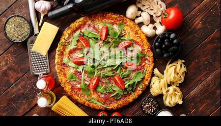 Il cibo italiano sfondo con pizza, pasta e verdure sul tavolo di legno Foto Stock