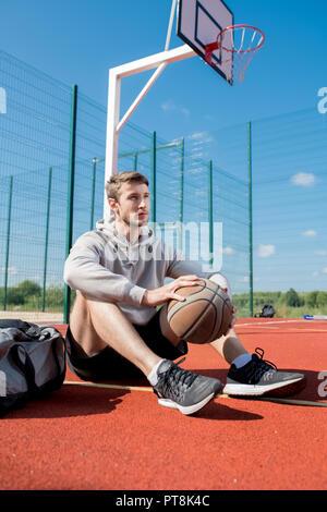 A piena lunghezza Ritratto di giovane contemporaneo uomo seduto sul pavimento nel campo da pallacanestro tenendo palla, spazio di copia Foto Stock