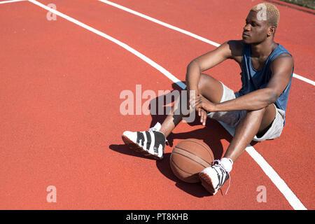 Angolo alto ritratto della moderna africana basket giocatore seduto sul pavimento in tribunale aperto con sfera, spazio di copia Foto Stock