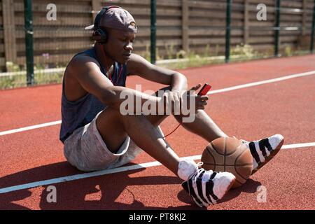 A piena lunghezza ritratto della moderna africana basket giocatore seduto sul pavimento in tribunale aperto e ascolto di musica tramite smartphone, spazio di copia Foto Stock