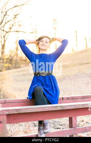 Giovane donna seduta in natura sulla parte superiore di legno dipinte di rosso ponte sul torrente fiume durante il tramonto, sunrise in autunno e inverno, retroilluminazione, retroilluminato capelli, Foto Stock