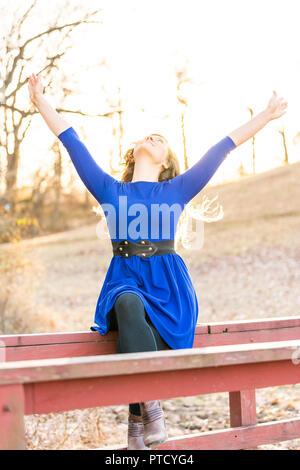 Giovane donna seduta in natura sulla parte superiore di legno dipinte di rosso ponte in sunset, autunno, retroilluminazione, retroilluminato capelli, sorridente, le mani alzate, proteso fino ho Foto Stock