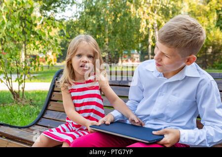 Fratello e Sorella nel parco su una panchina portar via un portatile da ogni altro Foto Stock