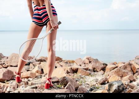 Vista ritagliata della giovane donna in costume da bagno a righe tenendo racchetta da tennis sulla spiaggia rocciosa Foto Stock