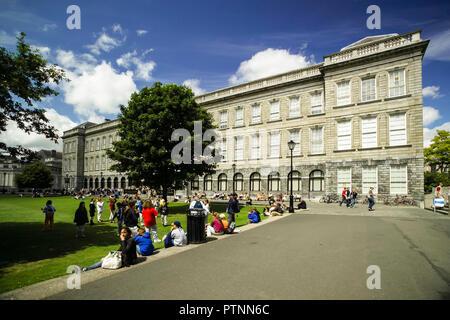 Le persone in un momento di relax a borsisti' piazza accanto alla vecchia libreria che ospita il Libro di Kells. Presso il Trinity College di Dublino. Foto Stock