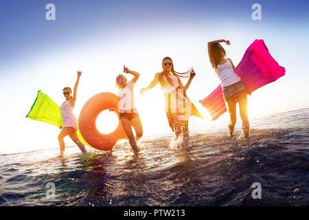 Felici le ragazze sono a piedi e divertirsi in acqua al tramonto la superficie con materassi di nuoto Foto Stock