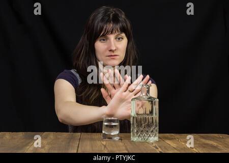 Ragazza ubriaca giace sul tavolo, mano mostra stop, sfondo nero, sul tavolo di alcole Foto Stock