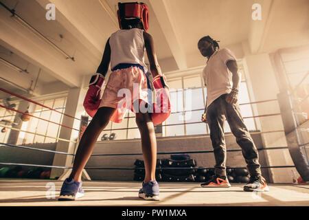 Boxing training di capretto con il suo allenatore all'interno di un anello di inscatolamento indossa guantoni da pugilato e copricapo. Il pugilato pullman con le tecniche di insegnamento della boxe per un capretto. Foto Stock