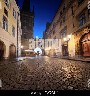 Via medievale che conducono verso la Città Minore torre del ponte verso il Ponte di Carlo su una notte piovosa a Praga, Repubblica Ceca