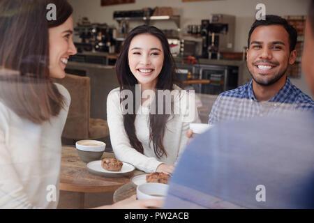Ridendo giovani amici adulti aventi un caffè a un coffee shop Foto Stock