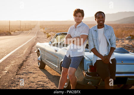 Ritratto di due amici maschi Godendo di viaggio su strada in piedi accanto al classico auto sulla strada del deserto Foto Stock