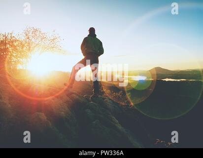Uomo che cammina sul bordo di una scogliera al vertice. Gamma Hrensko, Repubblica Ceca xxi di Seprtember 2018. Scalatore godendo di natura bellissima vista al sunse Foto Stock