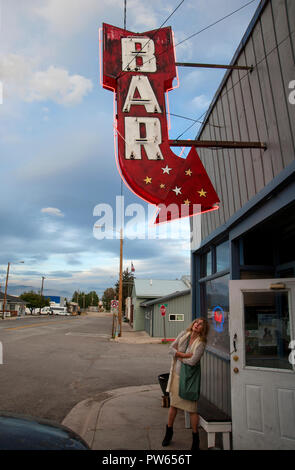 Donna lookingt presso un classico neon bar segno in una piccola città nel Montana, USA Foto Stock