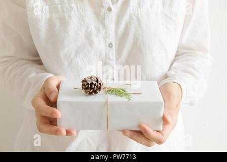Giovane donna caucasica detiene in mani confezione regalo avvolto in carta bianca legata con lo spago pigna ramoscello di ginepro. La luce del mattino colori pastello. Ne di natale Foto Stock