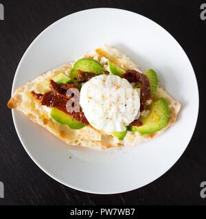 Uovo in camicia su pane tostato con un po' di avocado e pomodori secchi su piastra bianca. Foto Stock