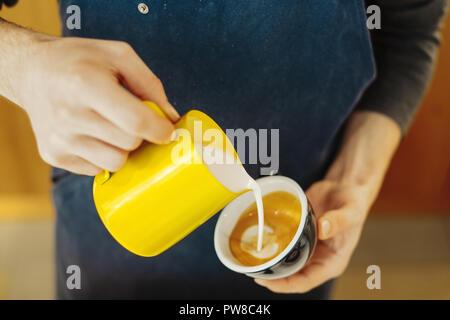 Chiusura del barista versando latte vaporizzato in una tazzina di caffè latte realizzazione tecnica. Foto Stock