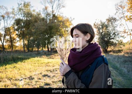 Giovane donna con un mazzetto di erbe di campo godendo bella tarda estate del giorno. Ritratto di donna con gli occhi chiusi retroilluminato in autunno sfondo Foto Stock