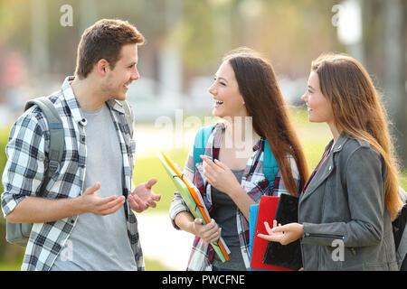 Tre Allievi felici stanno parlando all'aperto in strada Foto Stock