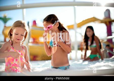 Due giovani ragazze a giocare in piscina insieme.