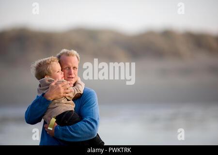 Ritratto di un uomo maturo abbraccia il suo giovane nipote su una spiaggia remota Foto Stock