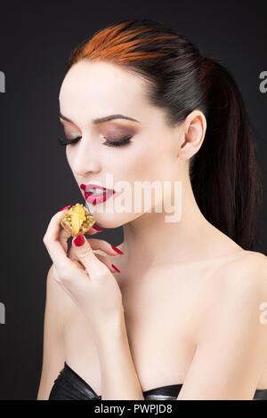 Girato a tenuta di una ragazza godendo di una torta al limone Foto Stock