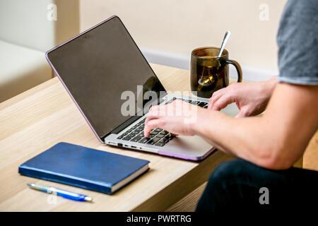 Concentrato giovane uomo con occhiali lavorando su un computer portatile in un ufficio a casa. Digitare su una tastiera e consente di scorrere il testo sul display. vista laterale