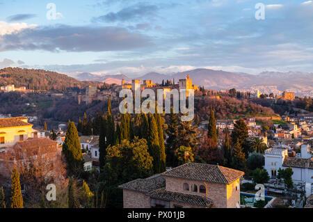 Alhambra Palace e l Unesco elencati quartiere Albaicin al tramonto con cime innevate della Sierra Nevada in background. Granada, Andalusia, Spagna Foto Stock