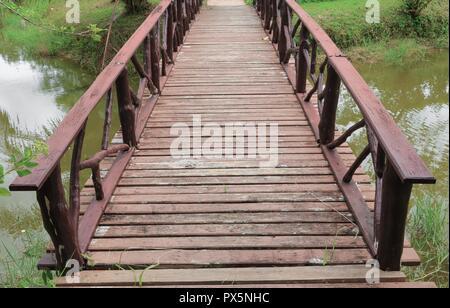Ponte di legno bella su un canale nel parco Foto Stock