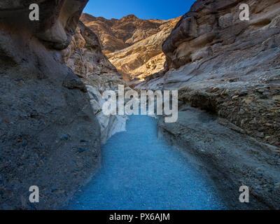 Sentiero attraverso il canyon del deserto, alla luce del sole sulle scogliere Foto Stock