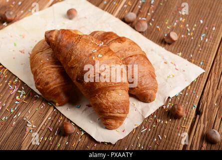 Croissant appena usciti dal forno su sfondo di legno Foto Stock