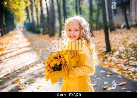 Poco bellissima ragazza con i capelli biondi in autunno sfondo Foto Stock