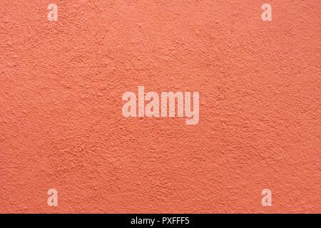 Parete in stucco - Maroon red stucco parete testurizzata sfondo con luce naturale. Foto Stock