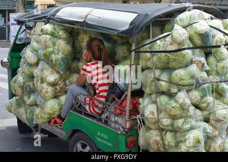 Un fornitore del mercato lascia Pak Klong Talad, un intero-vendita di verdura, frutta e il mercato dei fiori a Bangkok, Thailandia, lei-Tuk Tuk sovraccaricato con cavolo Foto Stock