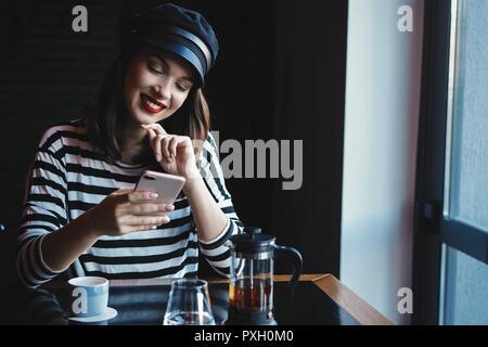 Ritratto di giovane donna bella utilizzando il suo telefono cellulare in cafe.