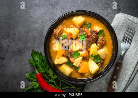 Gulasch con carne e verdure su sfondo nero. Foto Stock