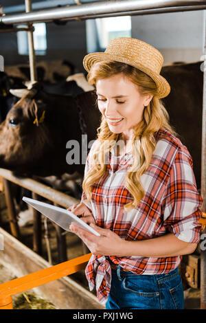 ... Attraente sorridente contadino nel cappello di paglia utilizzando  tablet in stabile Foto Stock 2e506ae0ee6d