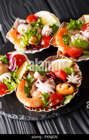 Gourmet a base di pesce insalata di gamberetti, polipetti, cozze, calamari e capesante in conchiglie di mare vicino sul piano verticale. Foto Stock