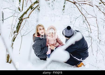 Elegante felice giovane famiglia passeggiate con il bambino sulla strada invernale, mamma, papà, bambino Foto Stock