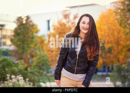 Excited donna giovane studente esterno ritratto di Autunno nel parco di università. Foto Stock