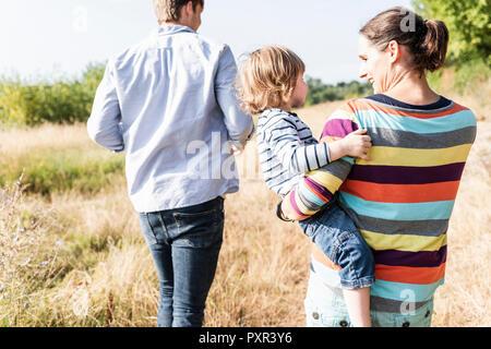 La famiglia felice passeggiate in riva al fiume e su un bel giorno di estate Foto Stock