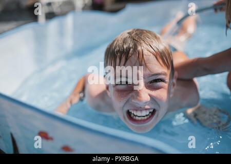 Ritratto di ragazzo giocando in piscina con sua sorella tirando funny faces Foto Stock
